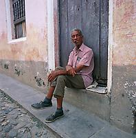 Cuba, Havana: Cuban Man in Street | Kuba, Havana: Einheimischer sitzt vor seiner Haustuer