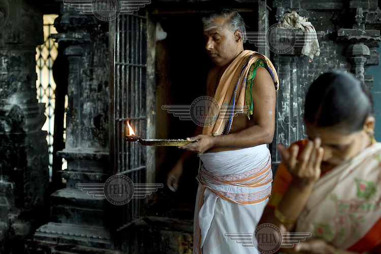 A priest by a shrine at the Murugan temple in Swamimalai gives ritual blessings to pilgrims.