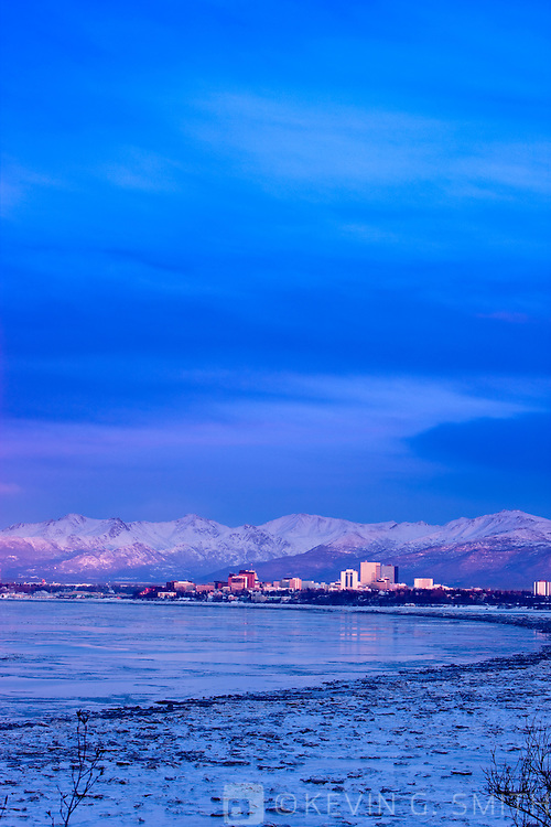 Photo of the Anchorage Skyline at sunset, aplenglow on the mountains and city, taken from Earthquake park, winter, Southcentral  Alaska, USA.