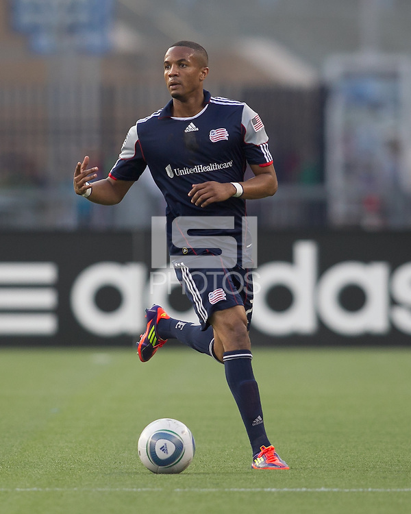 New England Revolution defender Darrius Barnes (25) brings the ball forward. In a Major League Soccer (MLS) match, the New England Revolution tied the Chicago Fire, 1-1, at Gillette Stadium on June 18, 2011.