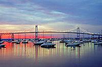 Boats rest amid the reflection of Newport Bridge at sunrise