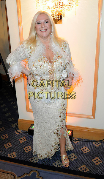 VANESSA FELTZ .Attending the World Food Awards (WFA), Park Lane Hilton Hotel, London, England, UK, 31st October 2009..full length white gold cream feather trim fluffy dress shrug cropped jacket hand on hip embroidered patterned corset sandals .CAP/FIN.©Steve Finn/Capital Pictures