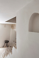 Smooth whitewashed walls contrast with the rough hewn stone steps of the interior