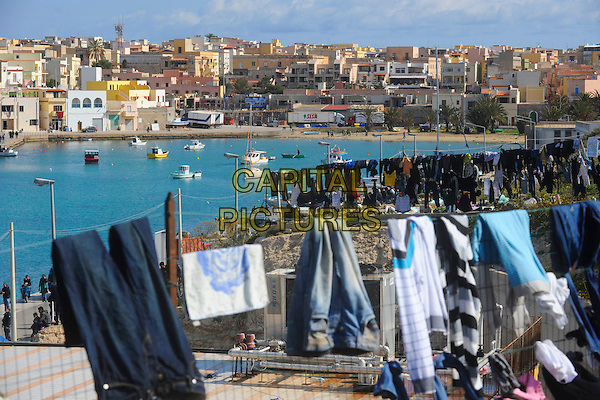 Immigrants in the Old Port area of Lampedusa, Italy 21st March 2011.atmosphere gv general view fence laundry clothes sitting.CAP/EPS/GG.©Giuseppe Giglia/EPS/Capital Pictures.