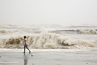 A man walks along the Galveston Seawall observing the huge waves generated by Hurricane Ike.