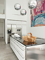 Tom Dixon mirror ball pendant lights hang above a central island in a stylish, contemporary white kitchen.
