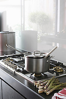 A stainless steel hob is set into a work surface of Black Zimbabwe granite