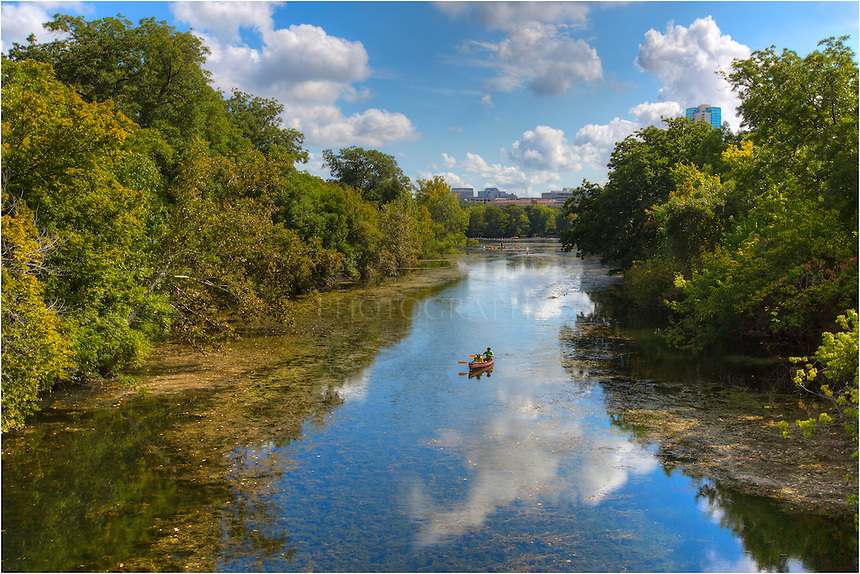 From the shadow of the Austin skyline, Zilker Park circles the Colorado River and Lady Bird Lake. On late summer days, you'll find folks out enjoying the morning. In this photograph from a beautiful Texas September morning, a canoer floats down the still water from Barton Springs that feeds into Lady Bird Lake.