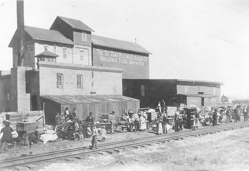 D&amp;RG 3-rail track with lots of migrant sugar beet workers waiting to load personal things - furniture aboard train.  In front of La Jara Milling &amp; Elevator Co. - Wholesale Flour, Grain, and Feed.<br /> D&amp;RG  La Jara, CO  Taken by Biglow, - 1911