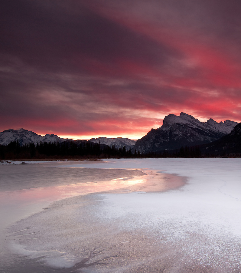 The sunrise lights up the clouds above Mount Rundle in a dramatic display of color along the shoreline of the Vermillion Lakes in the winter in Banff National Park, Alberta, Canada.