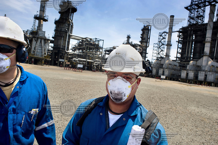 Oil workers wearing protective face masks at a refinery in Puerto la Cruz.