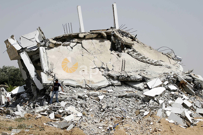 Palestinians inspect the rubble of a family house that was destroyed in an Israeli army operation near Khan Younis, in the southern Gaza Strip. Hamas militants later fired a barrage of mortar shells into southern Israel on Thursday, killing one person and wounding three others on a communal farm near the border with the Gaza Strip, Israeli officials said.