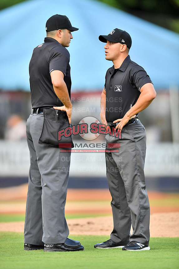 Home plate umpire Ben Fernandez and first base umpire Kelvis Velez discuss a call during a game between the Columbia Fireflies and the Asheville Tourists at McCormick Field on August 3, 2018 in Asheville, North Carolina. The Fireflies defeated the Tourists 6-3. (Tony Farlow/Four Seam Images)