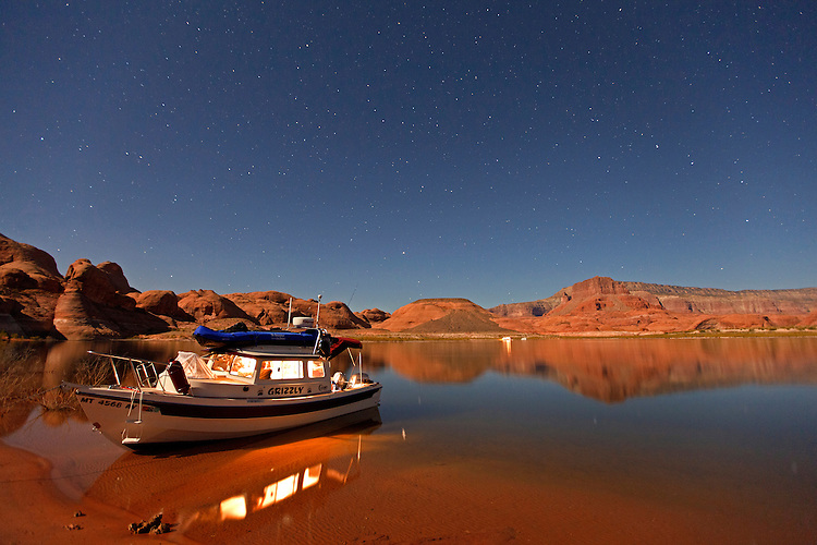 Beneath a starry night sky, a boat rests in Oak Canyon on Lake Powell within the Glen Canyon National Recreation Area, Utah, USA