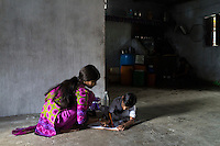 Hemant Jat, 6, finishes his homework with the help of his sister, Sapna Jat, 18, at home in Maheshwar, Khargone, Madhya Pradesh, India on 13 November 2014. Hemant, the son of a Fairtrade cotton farmer, wants to be a police man when he grows up and gets a 5% discount of school fees at the Vasudha school. His father Nandaram would be happy if Hemant took over the farm but if he does well in school, he could look for other careers. Photo by Suzanne Lee for Fairtrade