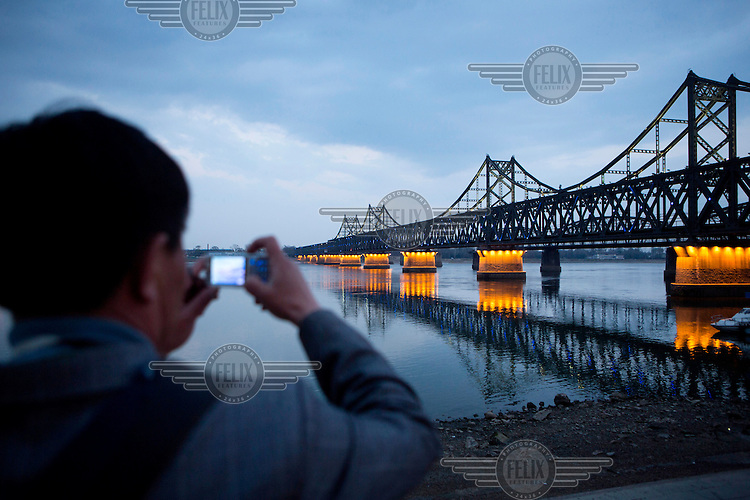 A man photographs the Sino-Korean Friendship Bridge that spans the Yalu River. It was originally built by the occupying Japanese between 1937 and 1943 and links the North Korean city of Sinuiju, on the far side, with the Chinese city of Dandong. /Felix Features