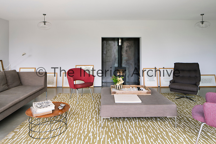 The sitting room is furnished in a minimalist style with a mixture of mid-century and contemporary pieces, such as a vintage Arne Jacobsen rug and a sofa and ottoman from B&B Italia. A wood burning stove is set in a recess on one side of the room.
