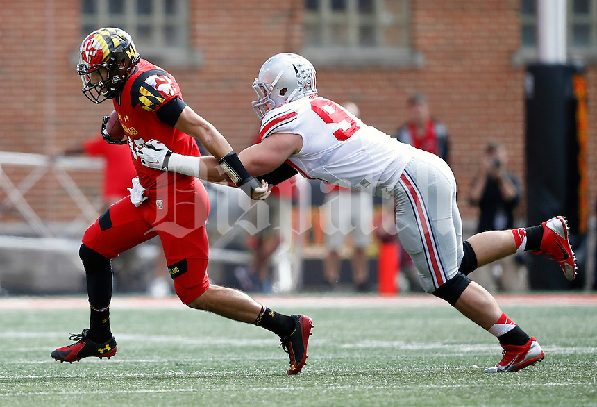 Ohio State Buckeyes defensive lineman Joey Bosa (97) reels in Maryland Terrapins quarterback C.J. Brown (16) during the second quarter of the NCAA football game at Byrd Stadium in College Park, Maryland on Oct. 4, 2014. (Adam Cairns / The Columbus Dispatch)