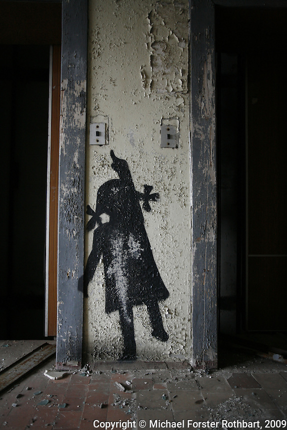 European artists have painted graffiti around Pripyat, mostly silhouettes suggesting the ghosts of former residents. This figure appears by the elevator on the 10th floor of an apartment building on Lazareva Street, opposite the post office. Some real-life former residents believe the graffiti defaces their town. Others see it as a way to remember the life that once filled their now-abandoned city.<br /> ------------------- <br /> This photograph is part the book of Would You Stay?, by Michael Forster Rothbart, published by TED Books in 2013. The photos come from Forster Rothbart&rsquo;s two long-term documentary photography projects, After Chernobyl and After Fukushima.<br /> &copy; Michael Forster Rothbart 2007-2013.<br /> www.afterchernobyl.com<br /> www.mfrphoto.com &bull; 607-267-4893 &bull; 607-436-2856 <br /> 34 Spruce St, Oneonta, NY 13820<br /> 86 Three Mile Pond Rd, Vassalboro, ME 04989<br /> info@mfrphoto.com<br /> Photo by: Michael Forster Rothbart<br /> Date:  3/2009    File#:  Canon 5D digital camera frame 60603