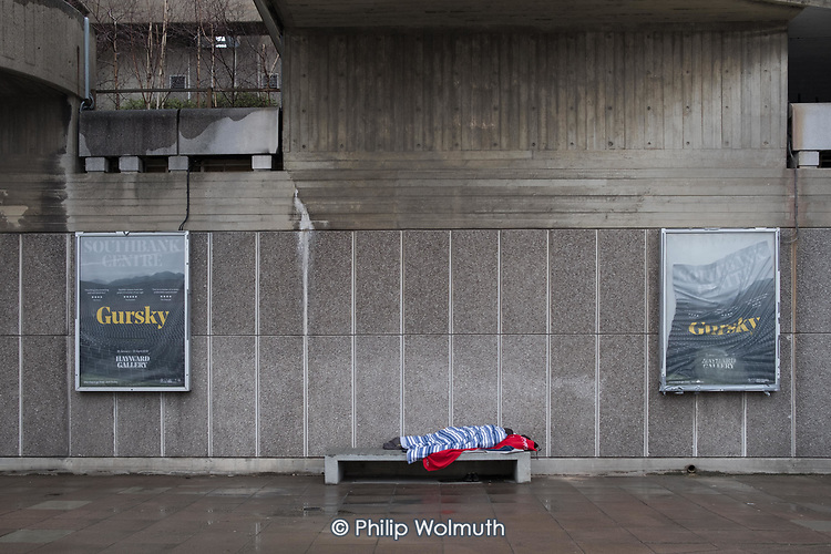 Rough sleeper on a concrete bench outside the Hayward Gallery, South Bank, London.