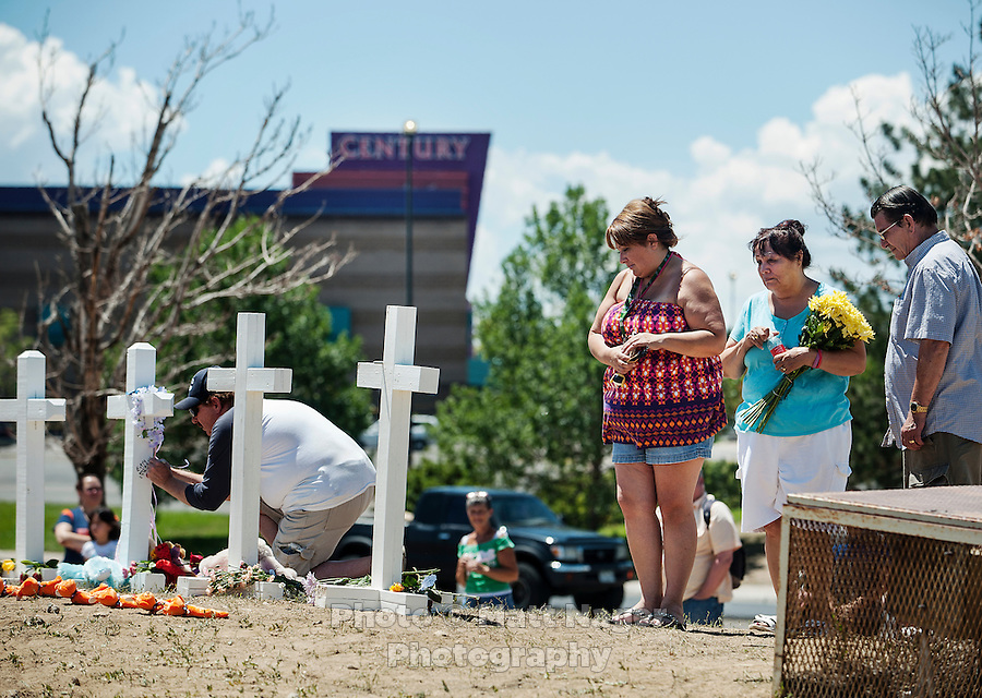 People visit a shrine for the victims of the shooting at an Aurora Century 16 theater where James Holmes (cq), 24, allegedly killed 12 people and wounded many more in Aurora, Colorado, Sunday, July 22, 2012. The shootings occurred during the midnight premiere of the new Dark Knight Batman movie...Photo by MATT NAGER