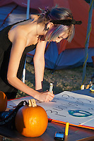 Carina inks in a new sign on Halloween at the Occupy Orange County - Irvine camp.
