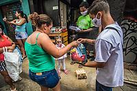 """RJ. Rio de Janeiro 28.06.2020 CORONAVÍRUS Jovens moradores de favela unidos num grupo denominado """"Marcha das Favelas"""",  para suprir a ausência do estado e as dificuldades da pandemia, dIstribuem sexta básica na favela do Jacaré, zona norte."""