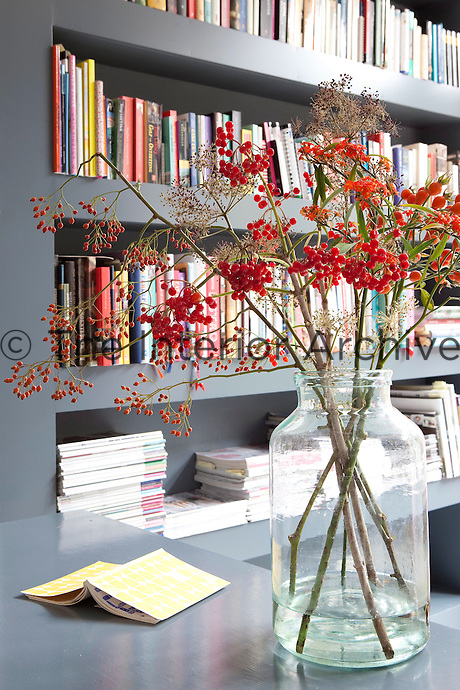 Bright red berries displayed in a vase create a bold contrast against the grey built-in bookshelves and desk in the living room