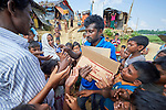 A Bangladeshi man distributes crackers to Rohingya refugees in the Jamtoli Refugee Camp near Cox's Bazar, Bangladesh. <br /> <br /> More than 600,000 Rohingya refugees have fled government-sanctioned violence in Myanmar for safety in this and other camps in Bangladesh.
