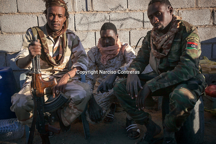 November 22, 2014 - Murzuq, Libya: Tebu tribal fighters at a check point on the road to Murzuq. Fighting around Southwest Ubari region ignited after Tuareg militias from Mali and Libya sized control over the vast oilfield installations aligned with the Third Force of Misrata armed forces. Since then raged battles have taken place between two factions: one faction of Tuareg fighters lead by Third Force from Misrata pushing to clean the region from the other faction of Tebu tribal fighters defending their controlled territory. (Photo/Narciso Contreras)