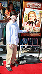 US actor Zach Mills points at this photo in the poster as he arrives at the world premiere of 'Kit Kittredge: An American Girl' at the Grove in Los Angeles, California on 14 June 2008. The film is based on the American Girl doll line and centers on Kit Kittredge, a young woman who grows up in the early years of the Great Depression.