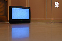 Television displaying static reflected in floor (Licence this image exclusively with Getty: http://www.gettyimages.com/detail/sb10066226m-001 )