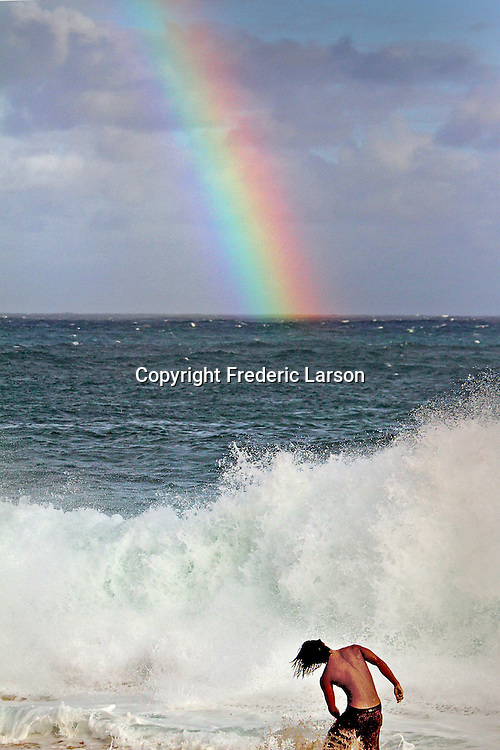 Surfers and beach goers enjoy the high waves and a rainbow at Sandy Beach in Honolulu, HI.