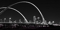 Dallas BW McDermott Bridge Pano - This is the Margaret McDermott Bridge BW pano in downtown Dallas. This Dallas skyline image in black and white after dark really pops the city. The McDermott bridge  is a steel bridge suspended with two arches over the Trinity River previously IH30 and is part of the Trinity project partially designed by Santiago Calatrava. This bridge is also designed to accomodate a pedestrian and bike path to join the the area other hike and bike trails. This was a night view which we made a black and white with the cityscape in the background after dark.