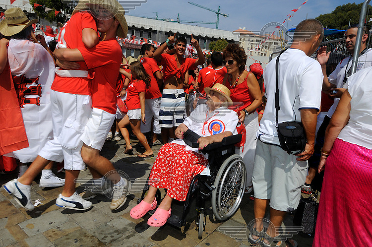 Diverse range of residents, including a woman in a wheelchair, dressed in the red and white of the Gibraltan flag during celebrations on Gibraltar National Day.