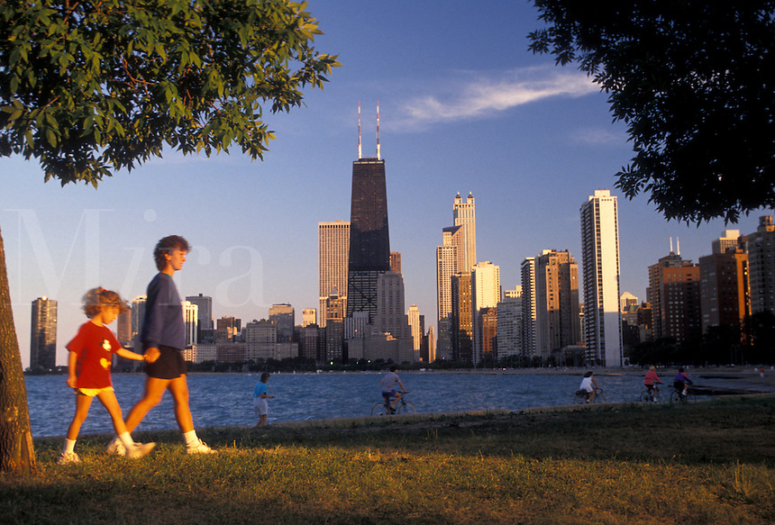 AJ2785, Chicago, skyline, Illinois, Skyline of downtown Chicago from Lincoln Park on Lake Michigan in the state of Illinois. Mother and daughter walking along the waterfront.