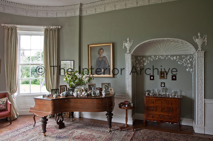 Delicate plasterwork vines and classical urns decorate the alcove in the drawing room