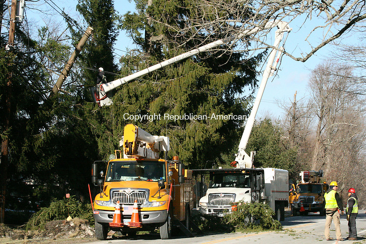 TORRINGTON, CT - 30 December, 2008 - 123008MO05 - Tree crews work Tuesday afternoon to remove a tree that had fallen onto power lines at the intersection of Torringford Street and Greenwoods Road in Torrington Tuesday morning, leaving about 300 people without power for several hours. High winds downed trees and limbs causing scattered outages across the region. More than 5,300 Connecticut Light and Power customers were without power at 4 p.m. Jim Moore Republican-American.