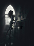 Sunlit silhouette of a beautiful nude woman profile on a staircase in a house Image © MaximImages, License at https://www.maximimages.com