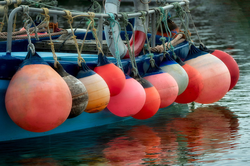 Boat floats in Mousehole haerbor. Cornwall, England