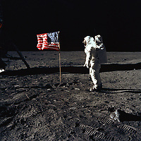 """Moon, July 20, 1969 - <br /> Astronaut Buzz Aldrin, lunar module pilot of the first lunar landing mission, poses for a photograph beside the deployed United States flag during an Apollo 11 Extravehicular Activity (EVA) on the lunar surface. The Lunar Module (LM) is on the left, and the footprints of the astronauts are clearly visible in the soil of the Moon. Astronaut Neil A. Armstrong, commander, took this picture with a 70mm Hasselblad lunar surface camera. While astronauts Armstrong and Aldrin descended in the LM, the """"Eagle"""", to explore the Sea of Tranquility region of the Moon, astronaut Michael Collins, command module pilot, remained with the Command and Service Modules (CSM) """"Columbia"""" in lunar-orbit."""