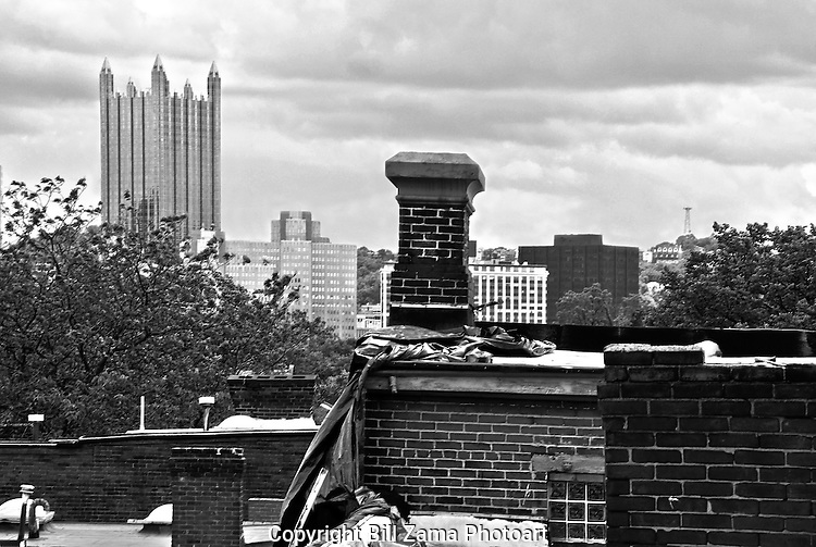 Old crooked chimney on a Pittsburgh rooftop with the PPG Building in the background.