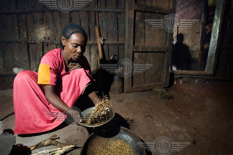 The wife of a local coffee farmer prepares coffee beans in preparation for the traditional daily coffee ceremony.