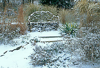 Grapevine bench in winter garden with snow highlighting the lines of the twisting wood with ornamental grass and aloe.