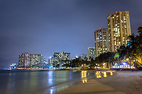 Hotels with lights reflecting off the water at night at Kuhio Beach in Waikiki, Oahu