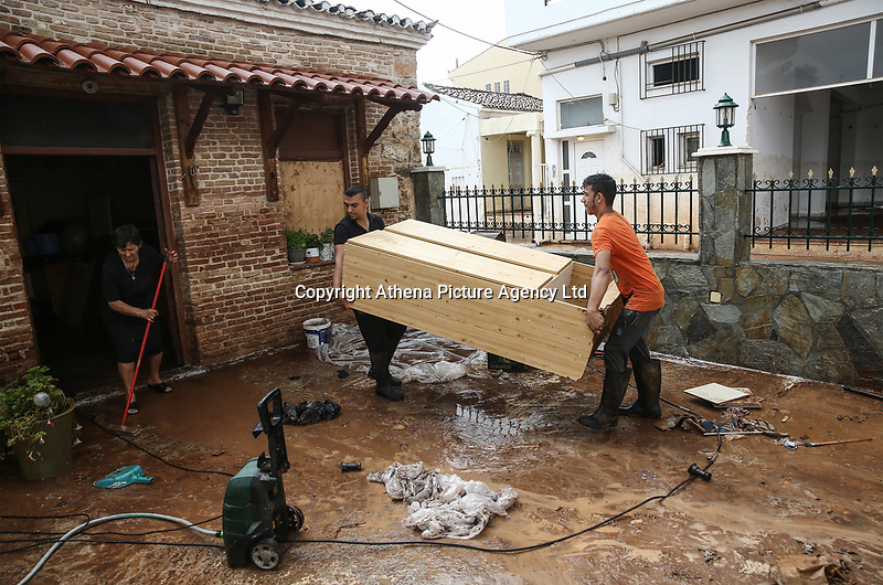 Pictured: Two people carry furniture because of the floods in the Mandra area, in the outskirts of Athens, Greece. Wednesday 27 June 2018<br /> Re: Flashflooding has been caused by storm Nefeli in parts of Greece.