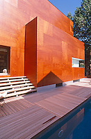 Exterior of the wood-clad property from the teak decking which surrounds the swimming pool