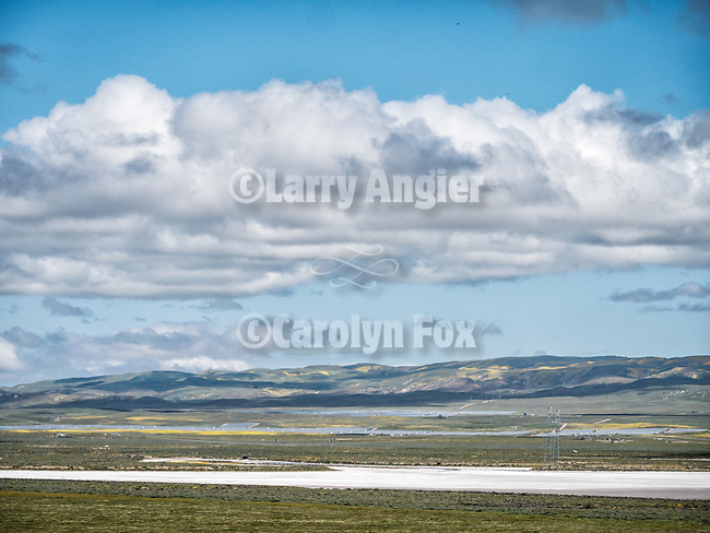 Spring, Soda Lake and clouds, Temblor Range, golden wildflowers, spring, Carrizo Plain, San Luis Obispo County, Calif.<br /> <br /> Solar energy farms cover the valley floor north of the lake playa