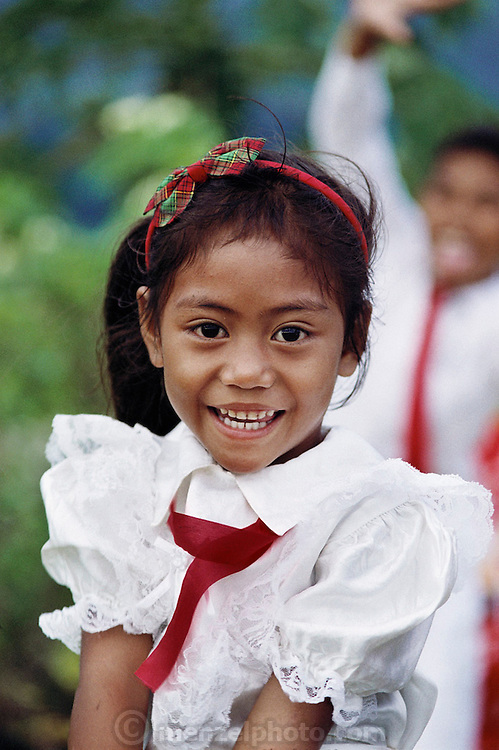 Dressed in her White Sunday finery, a young member of the extended Lagavale family is happy that church services are over. White Sunday (also called Children's Day), is celebrated on the second Sunday of October each year. In this tradition brought to Western Samoa by the London Missionary Society, the children receive new clothes and gifts, and festive games are played. Most attend church services and then gather for family feasts that feature foods like pork, taro, and coconuts. The Lagavale family lives in a 720-square-foot tin-roofed open-air house with a detached cookhouse in Poutasi Village, Western Samoa. Material World Project.