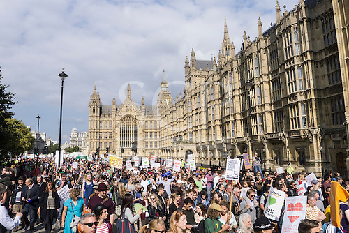 A mass of protesters with placards march in front of the Houses of Parliament during the Climate Change demonstration, London, 21st September 2014. © Sue Cunningham